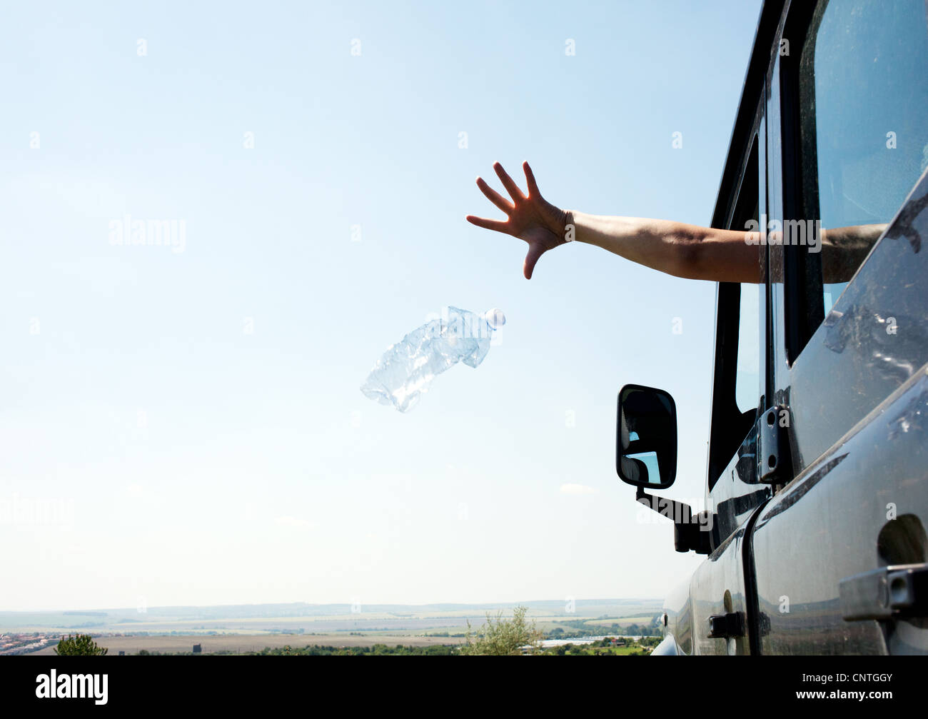 Woman throwing bottle out car window - Stock Image