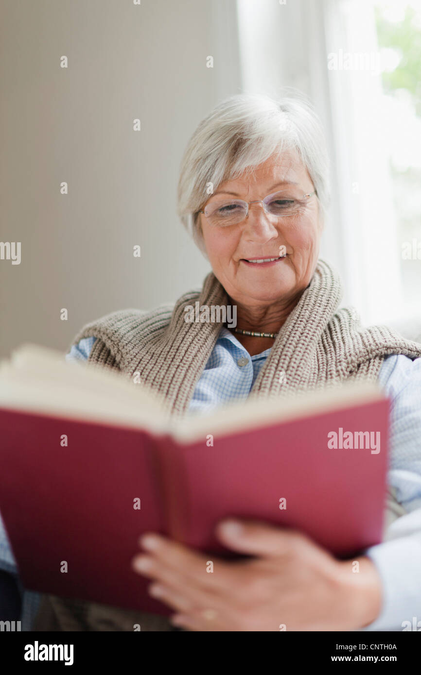 Smiling older woman reading book - Stock Image
