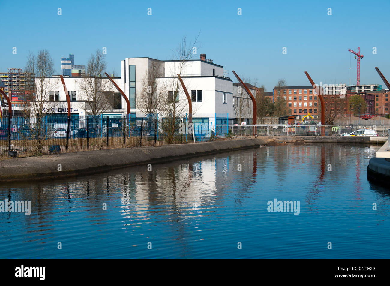 Ancoats Primary Care Centre and the canal arm on Old Mill Street, New Islington, Manchester, England, UK - Stock Image