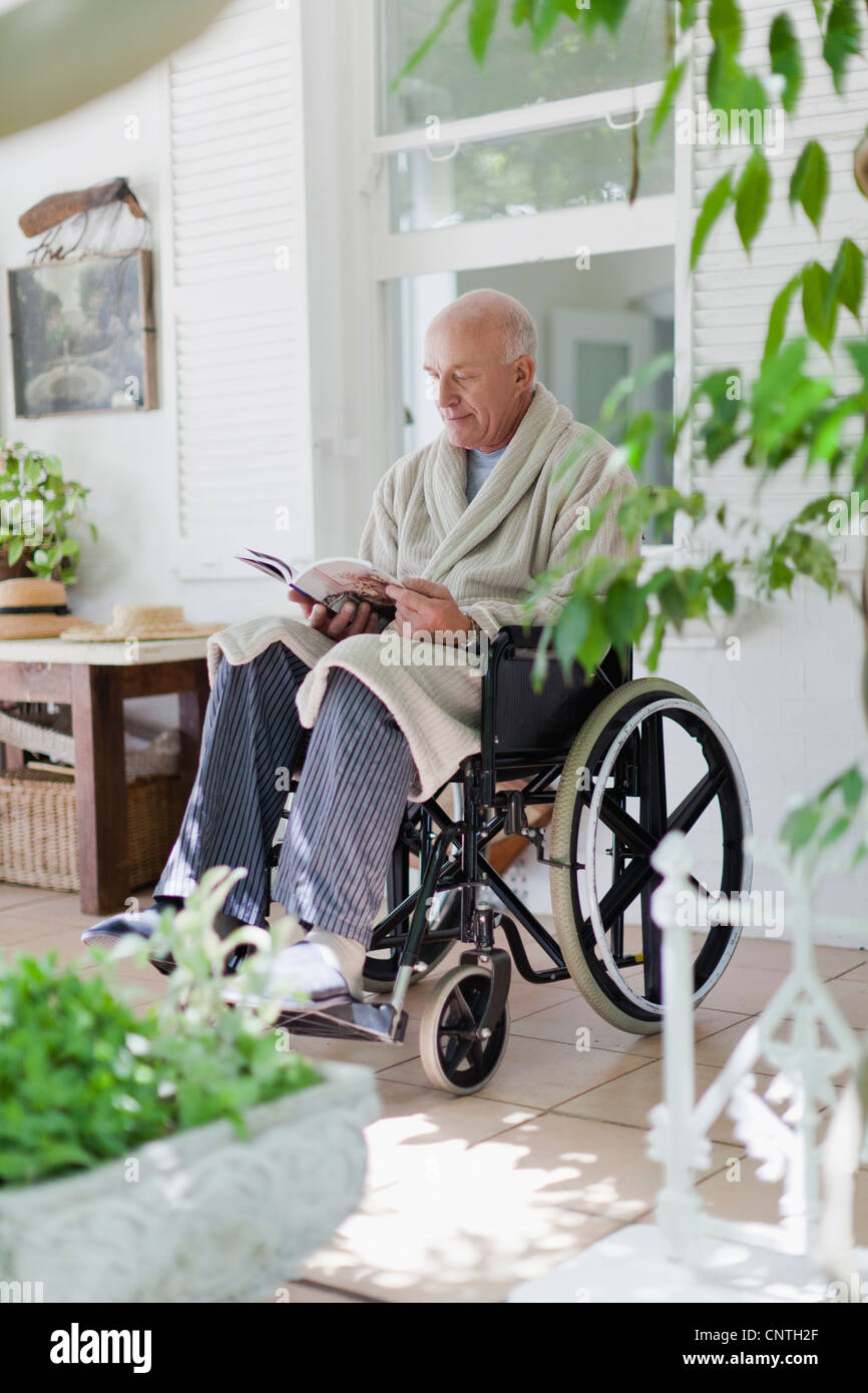 Older man reading in wheelchair - Stock Image