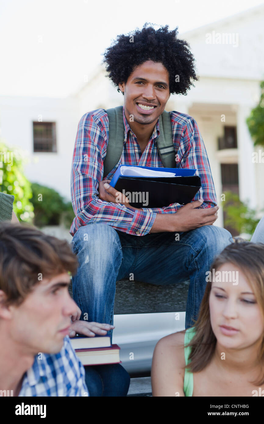 Man sitting with colleagues on campus - Stock Image