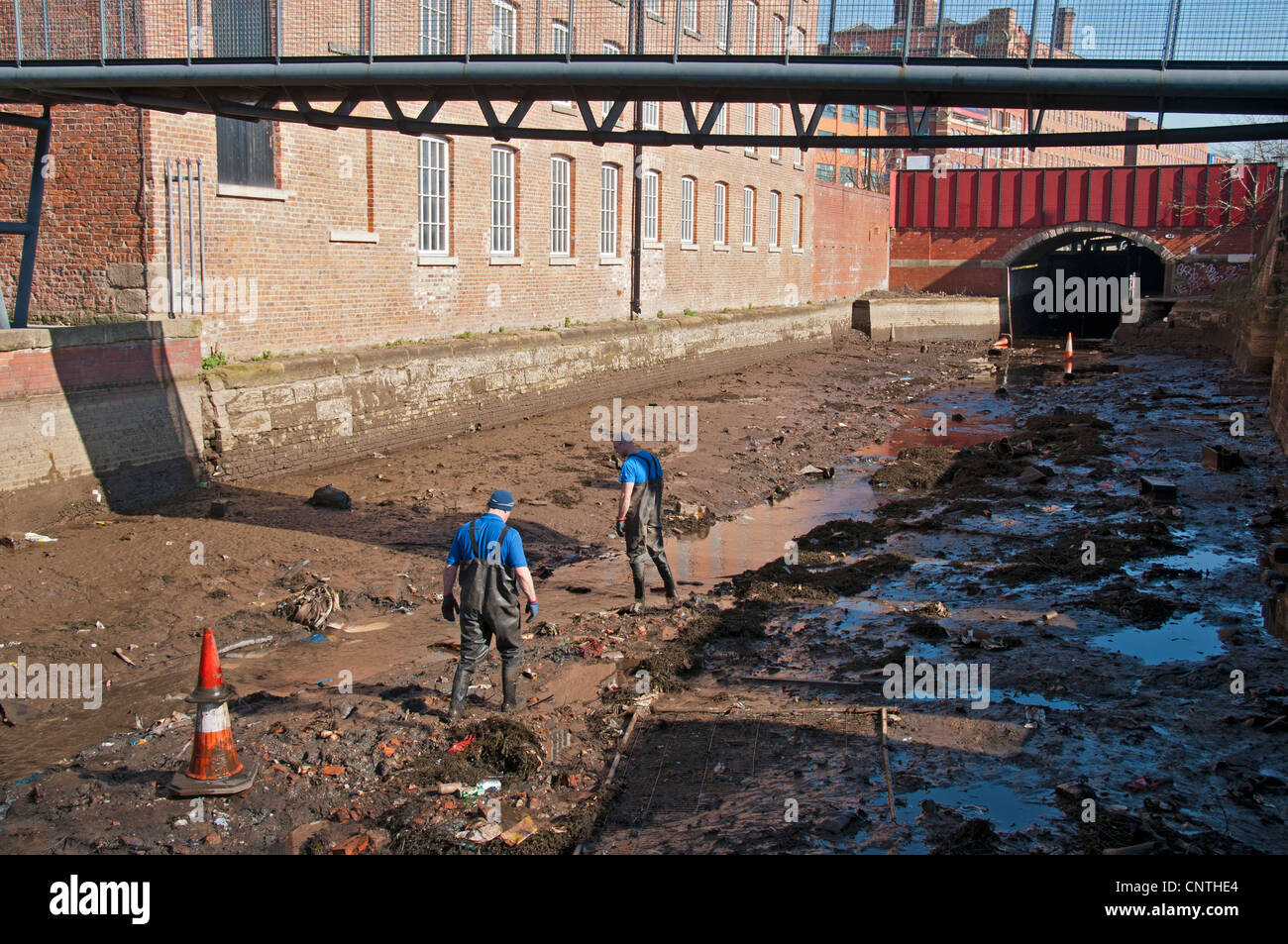 British Waterways workers clearing rubbish from a drained section of the Rochdale Canal, Ancoats, Manchester, England, - Stock Image
