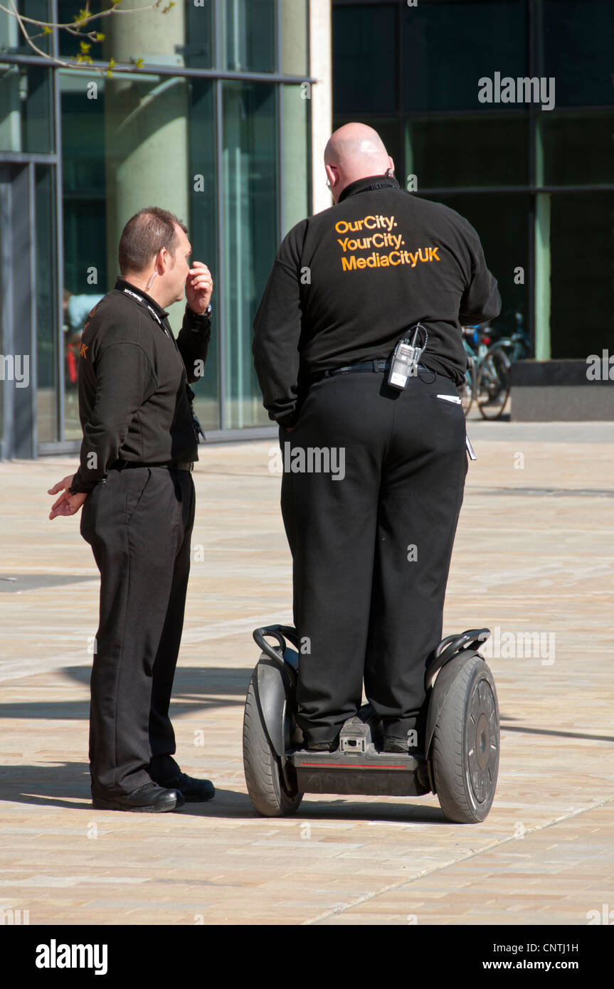 Two security guards, one on a Segway, at MediaCityUK, Salford Quays, Manchester, England, UK Stock Photo