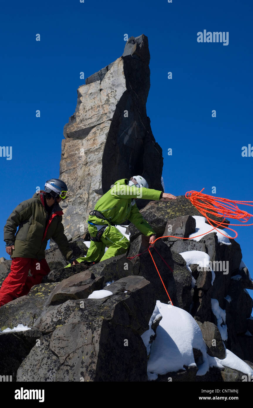 two ski alpinists with helmets and ski goggles climbing in the mountains, throwing the rope, France, Alps - Stock Image