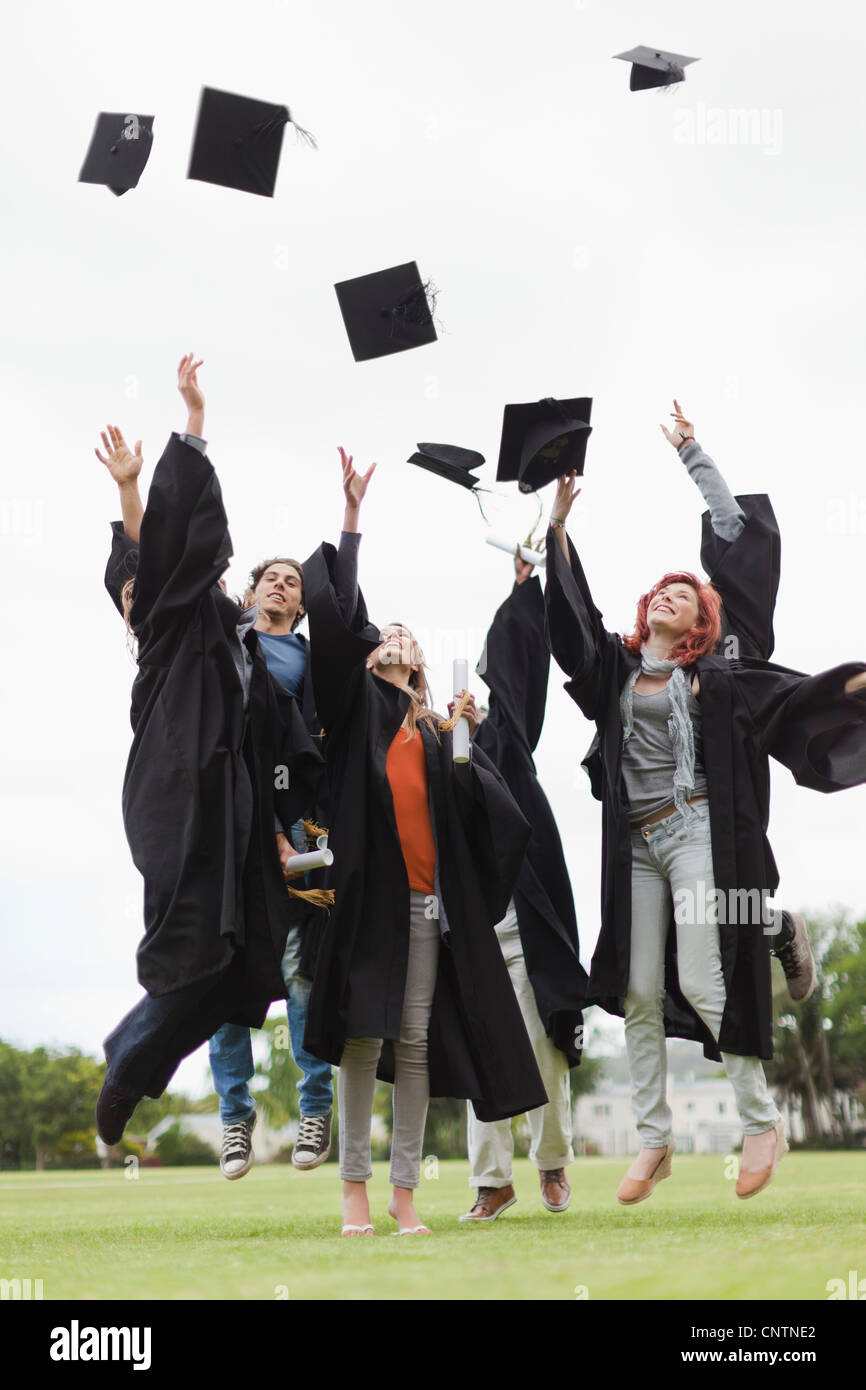 Graduates throwing caps in the air - Stock Image