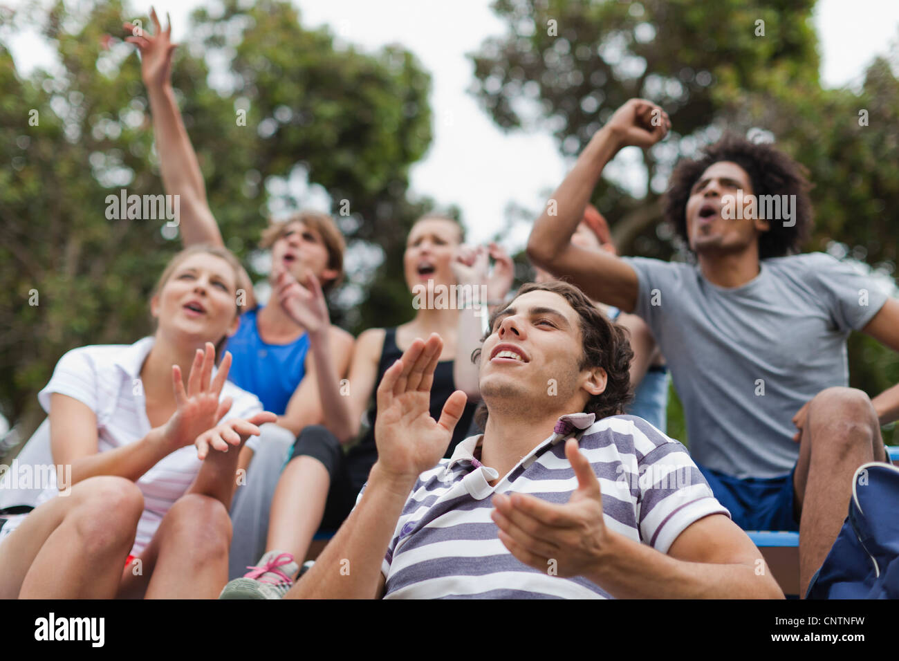Friends cheering at sporting event - Stock Image
