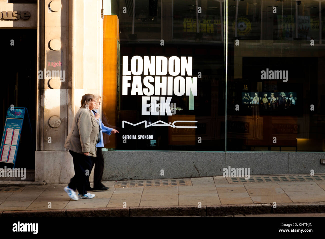 Humourous view of London Fashion Week shop window misspelling with two women shoppers and several models on a tv - Stock Image