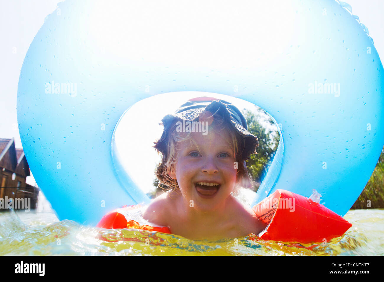 Boy playing with inner tube in pool - Stock Image