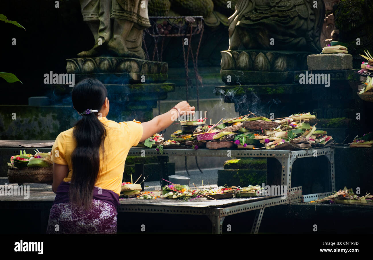 At the Ubud, Bali Market Temple, Hindu worshipers come to pray and leave offerings, called canang, as gifts to the - Stock Image