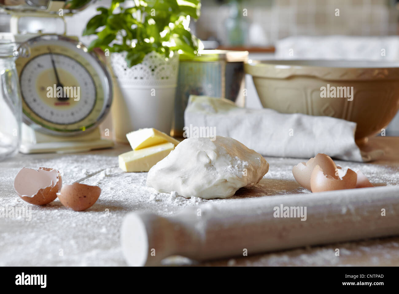 Pizza dough and eggs in messy kitchen - Stock Image