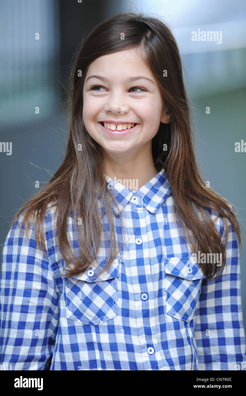 Smiling girl wearing plaid shirt - Stock Image