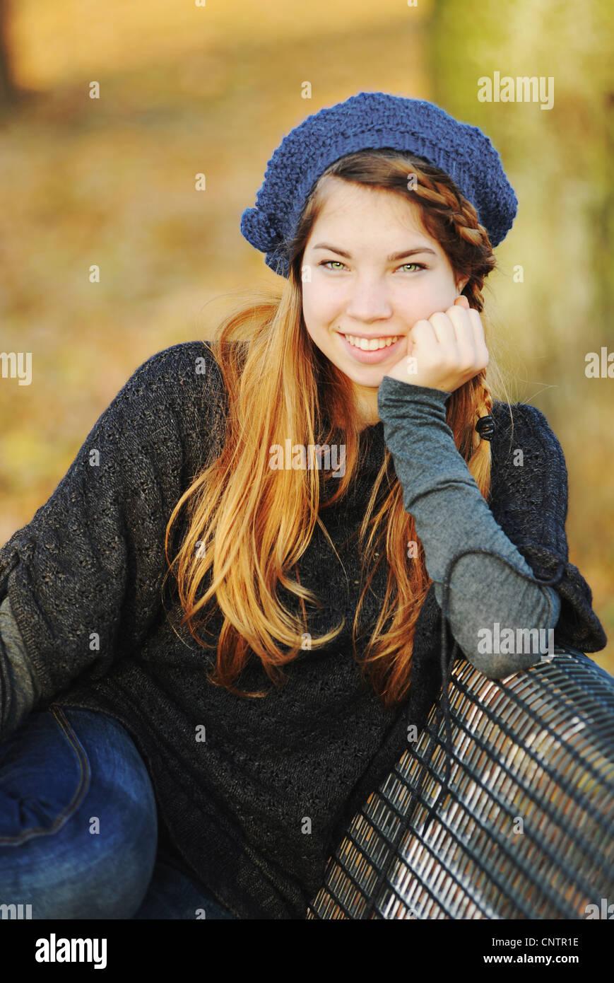 Teenage girl sitting on park bench Stock Photo