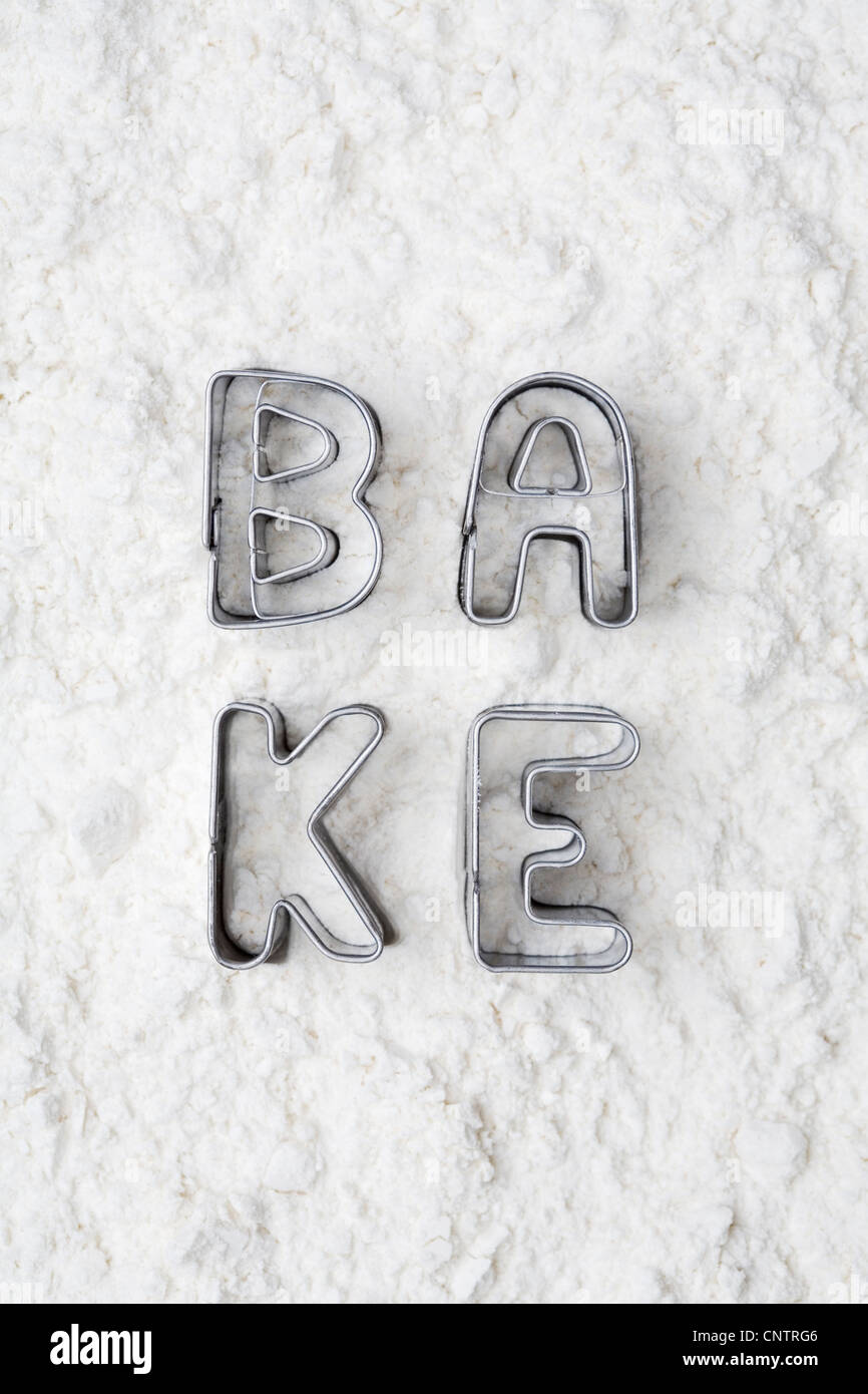 Cookie cutters spelling bake in flour Stock Photo