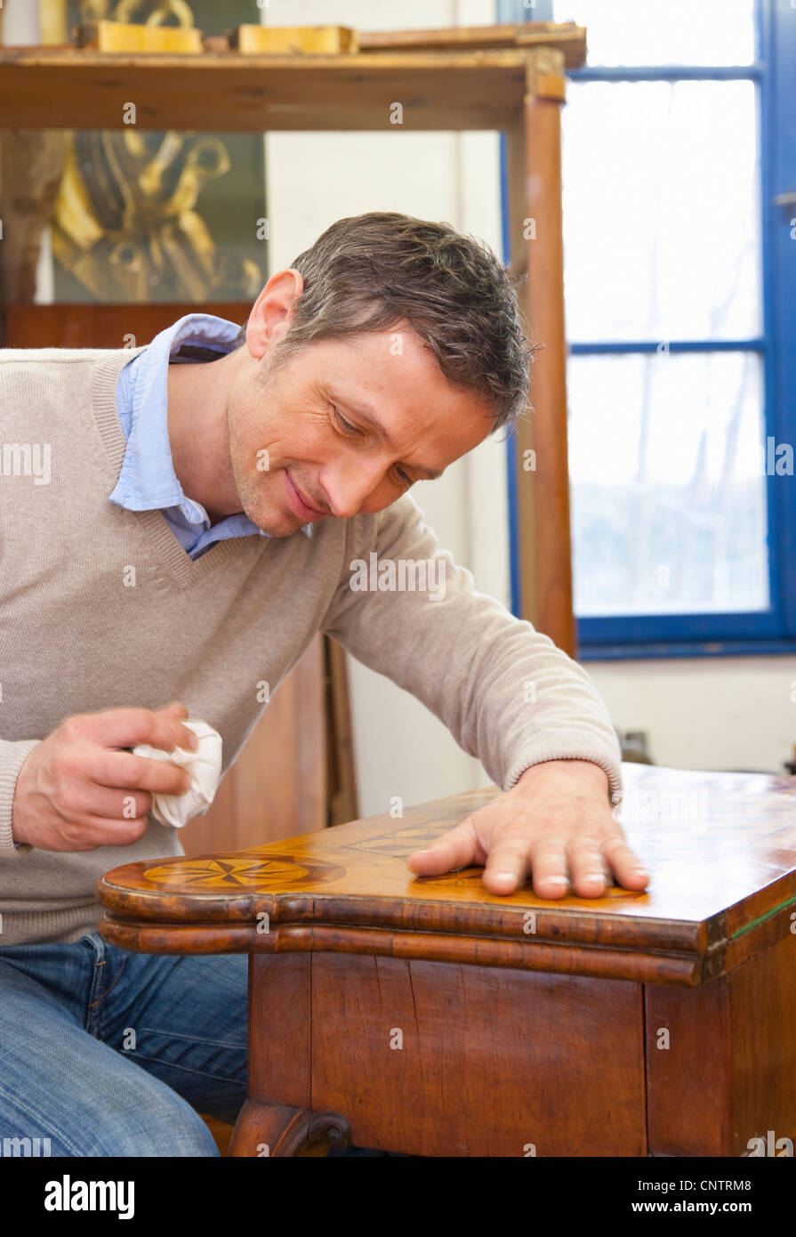 Carpenter buffing wooden table Stock Photo