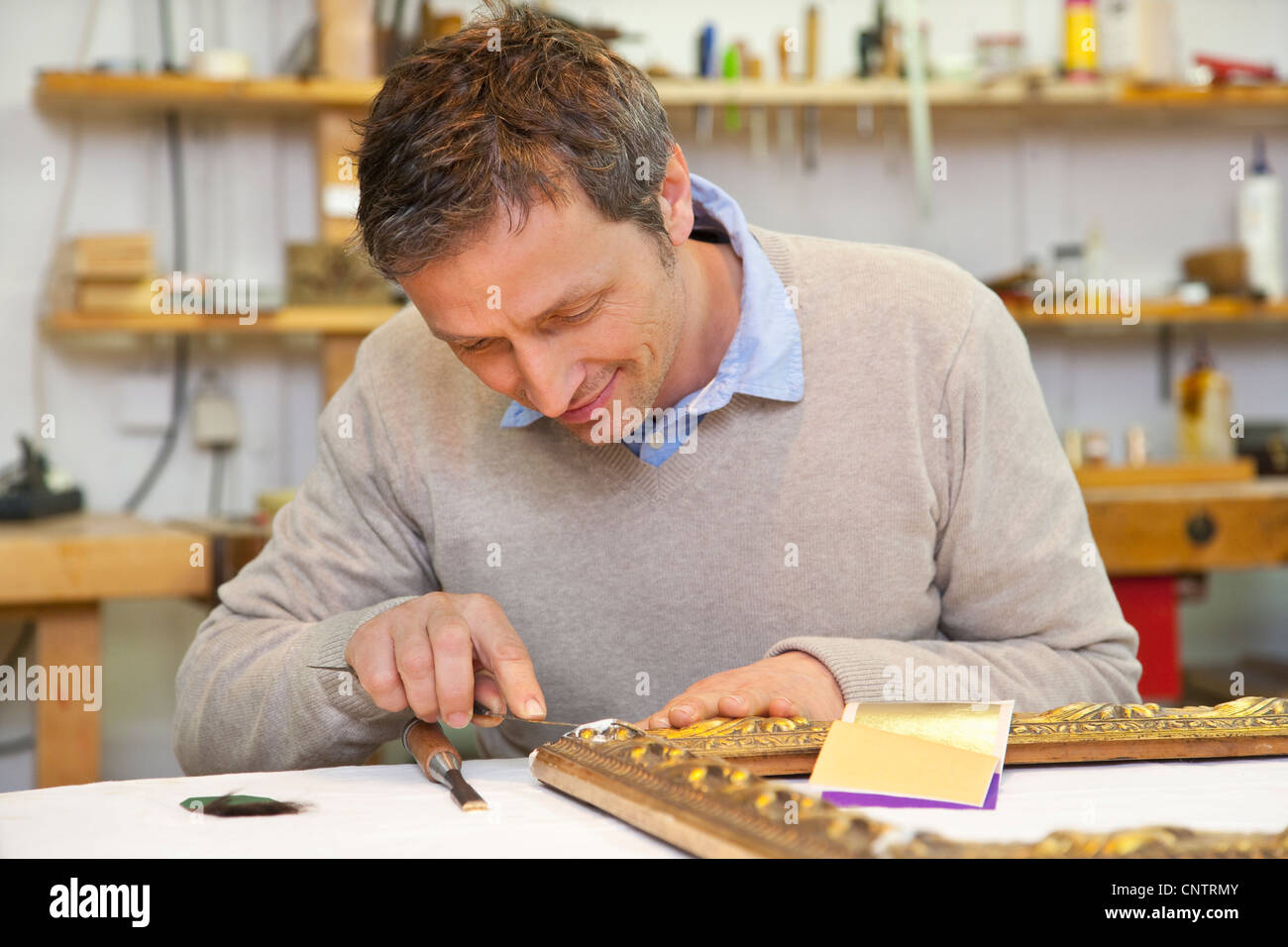 Carpenter working in shop - Stock Image
