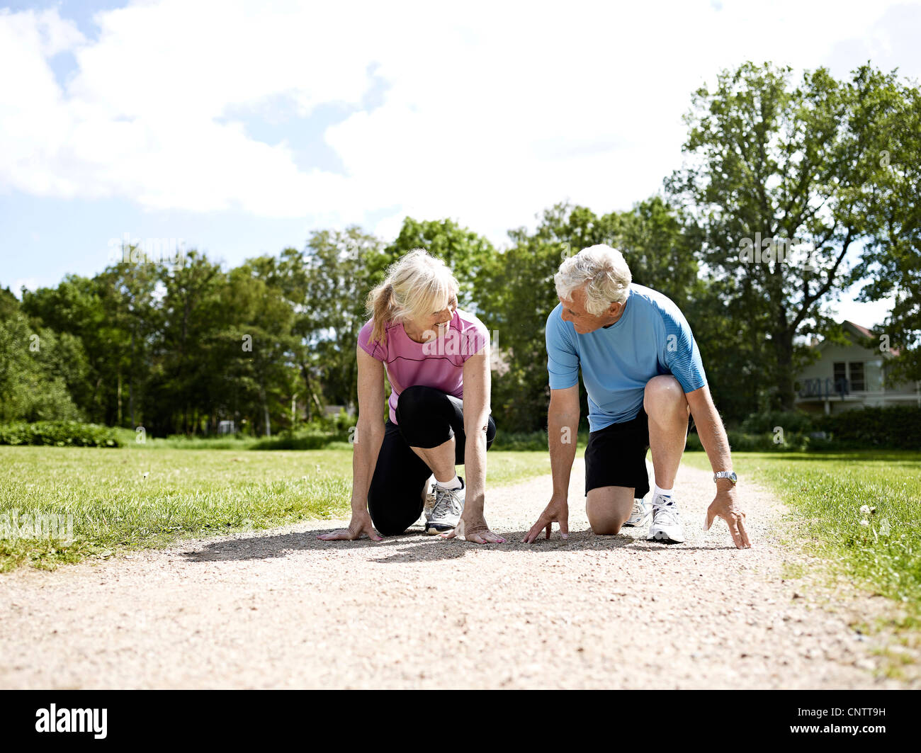 Older couple crouched in start position - Stock Image