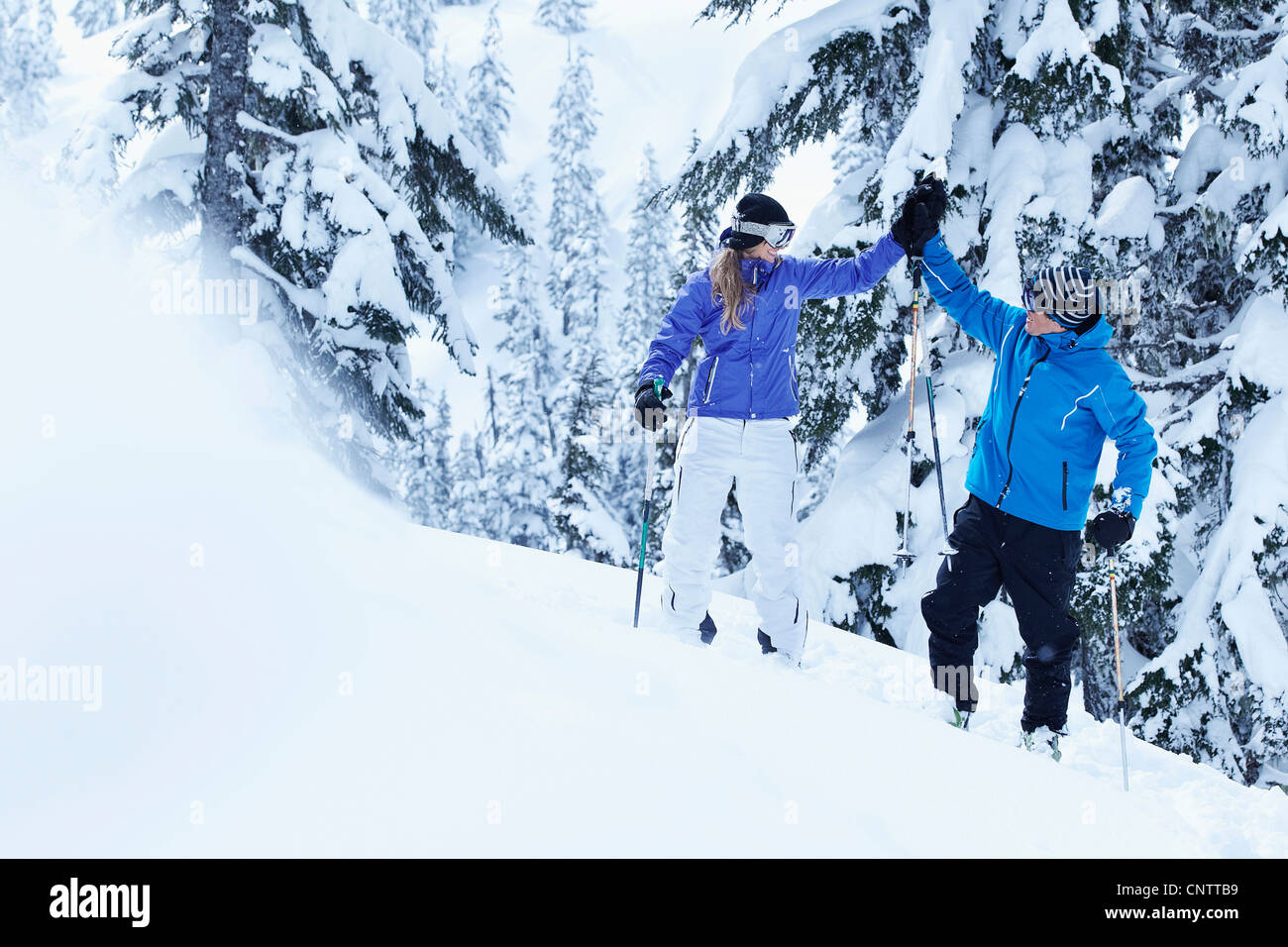 Skiers high-fiving on snowy mountain Stock Photo