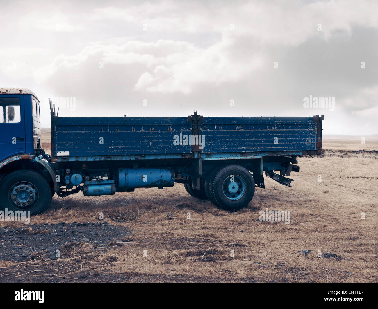 Blue truck parked in dry field - Stock Image