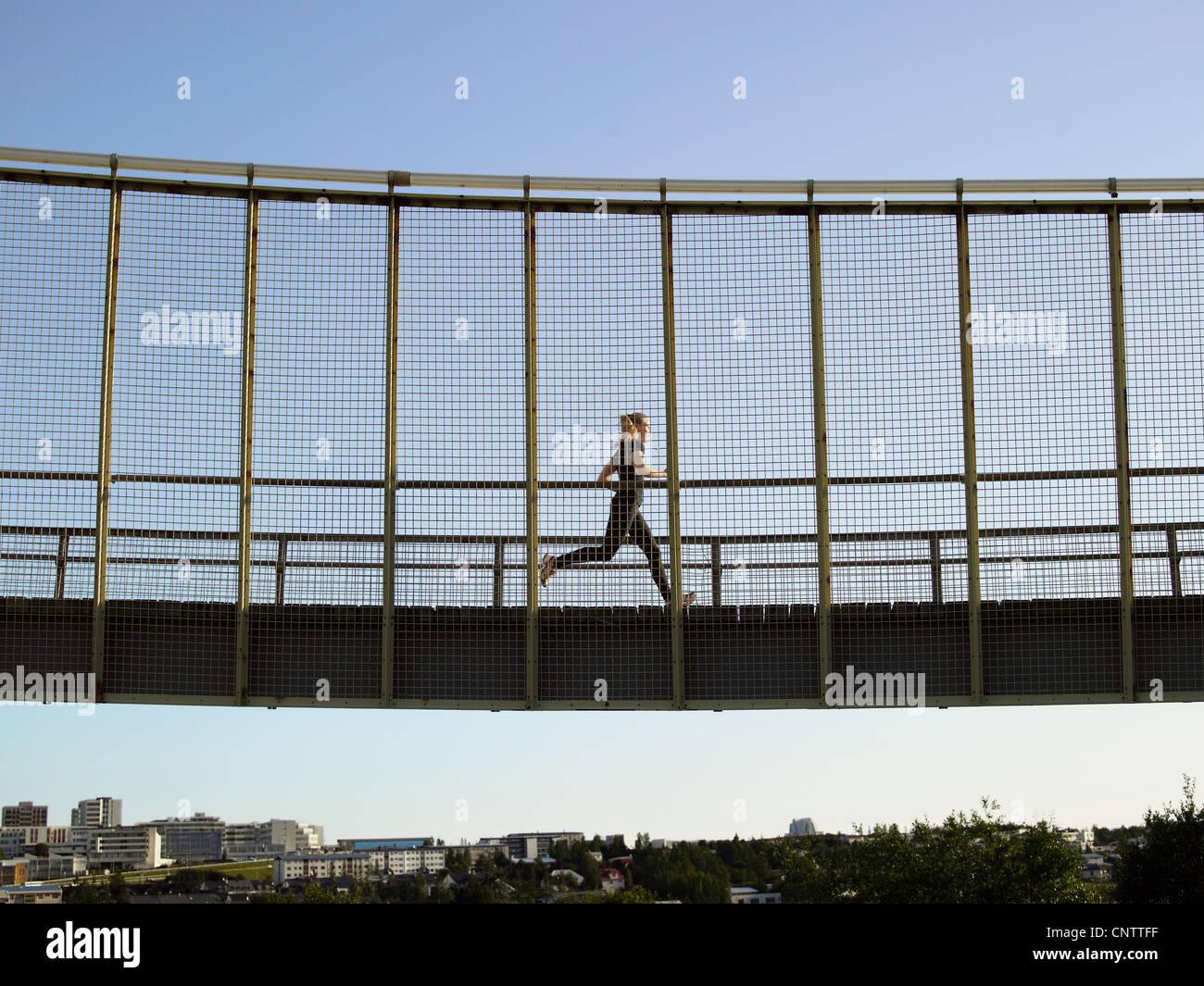 Runner crossing skybridge - Stock Image
