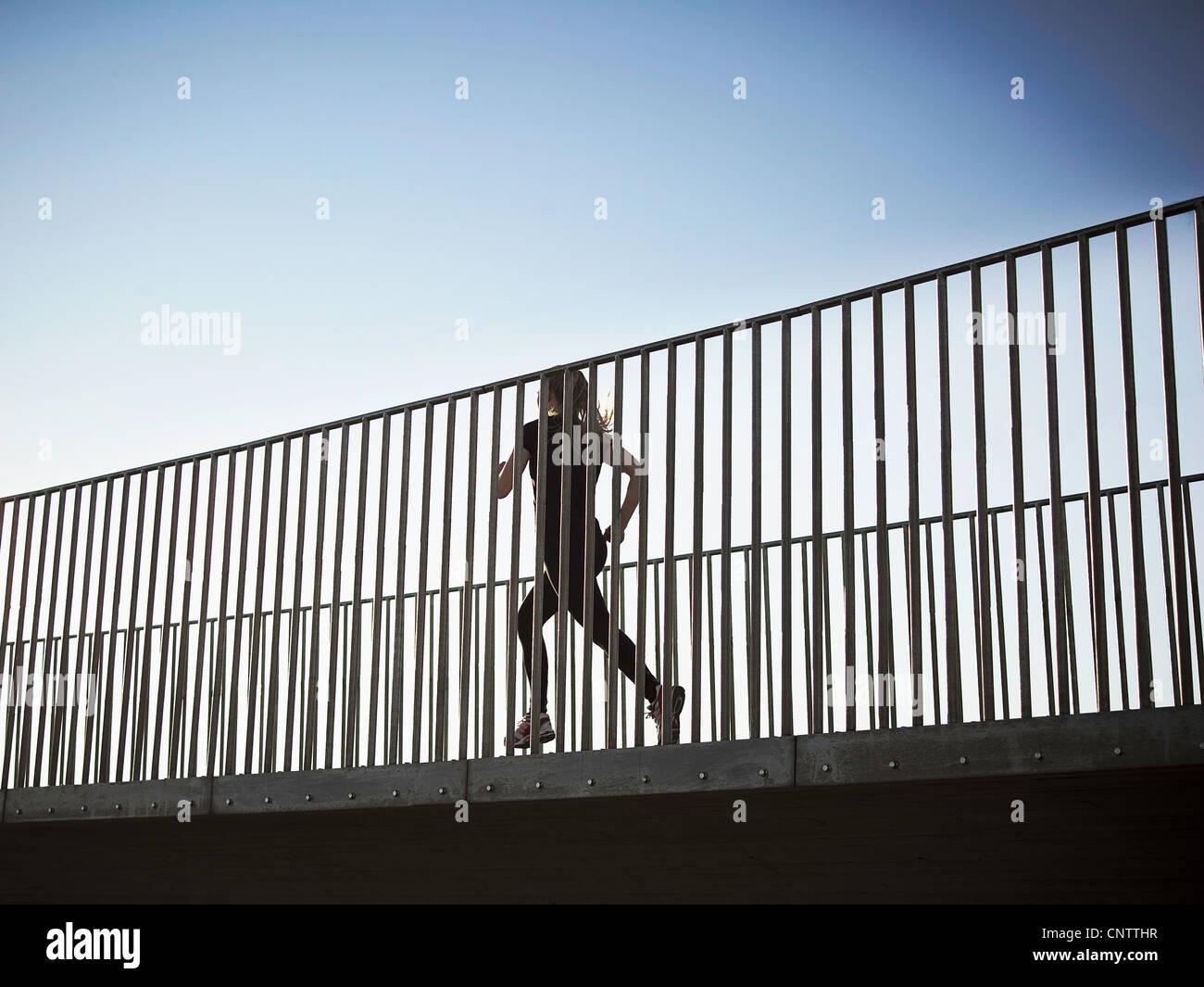 Woman running on skybridge - Stock Image