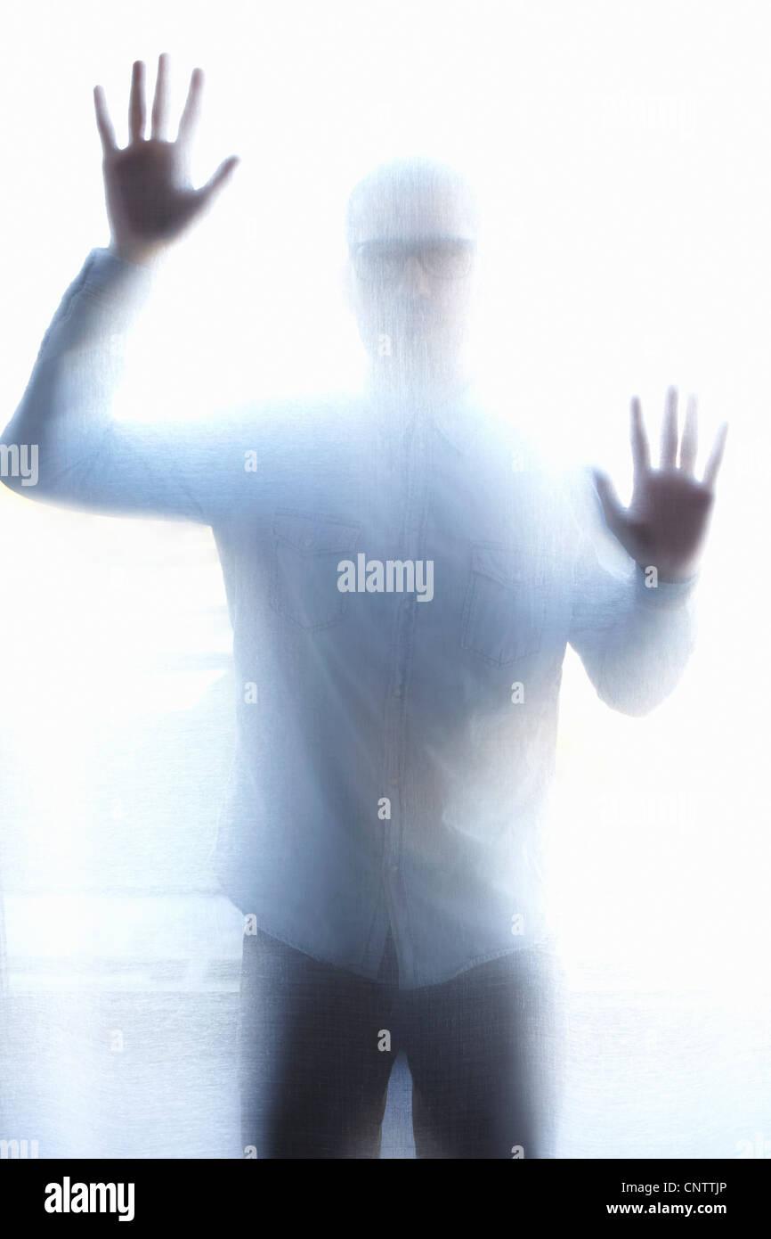Man standing behind thin screen - Stock Image