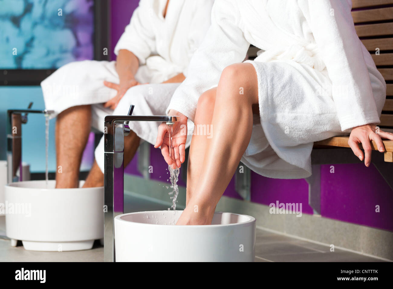 Couple - man and woman - having hydrotherapy water footbath in spa setting Stock Photo