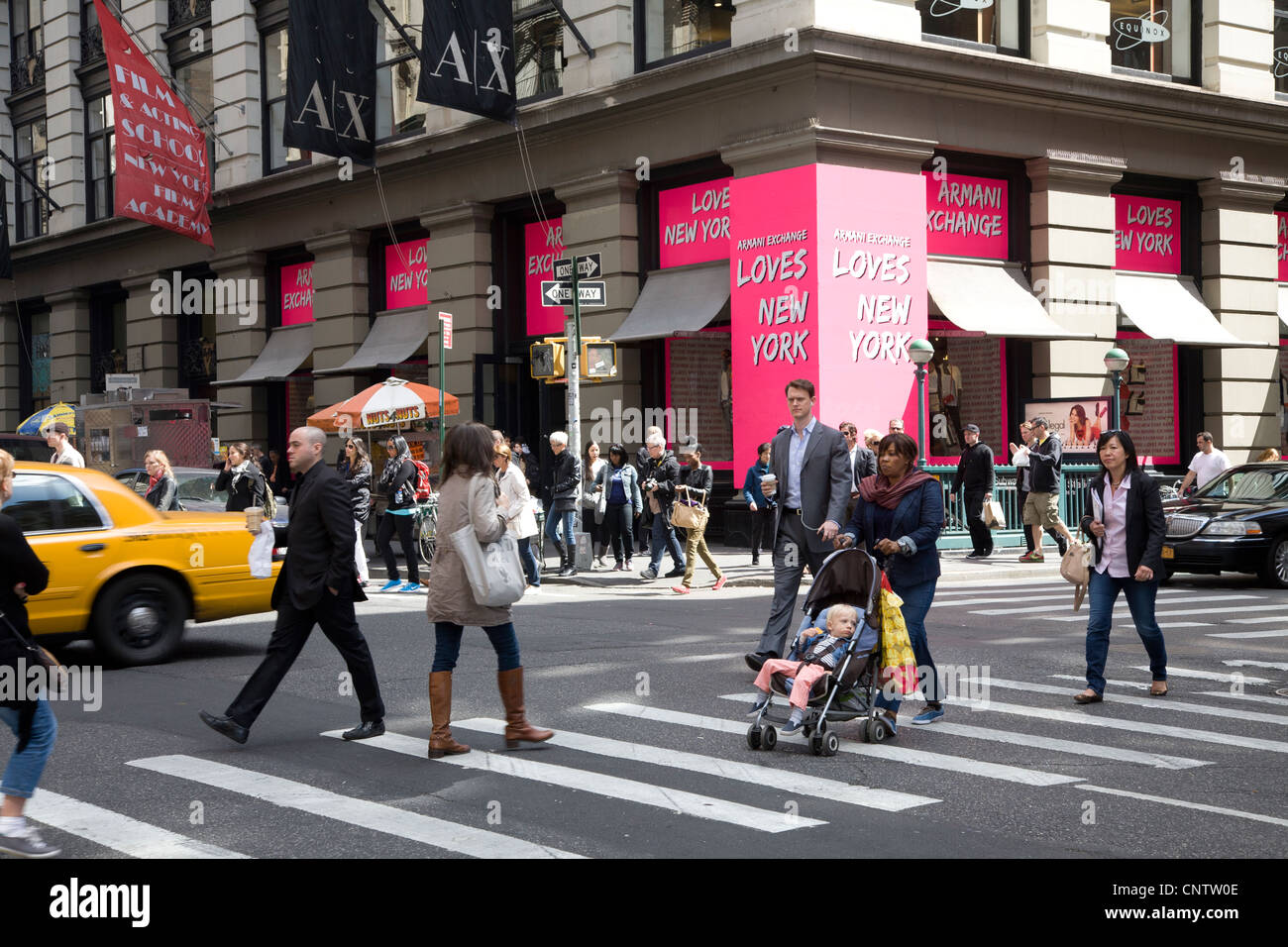 People in the crosswalk at 5th Avenue and 51st St. in NYC. - Stock Image