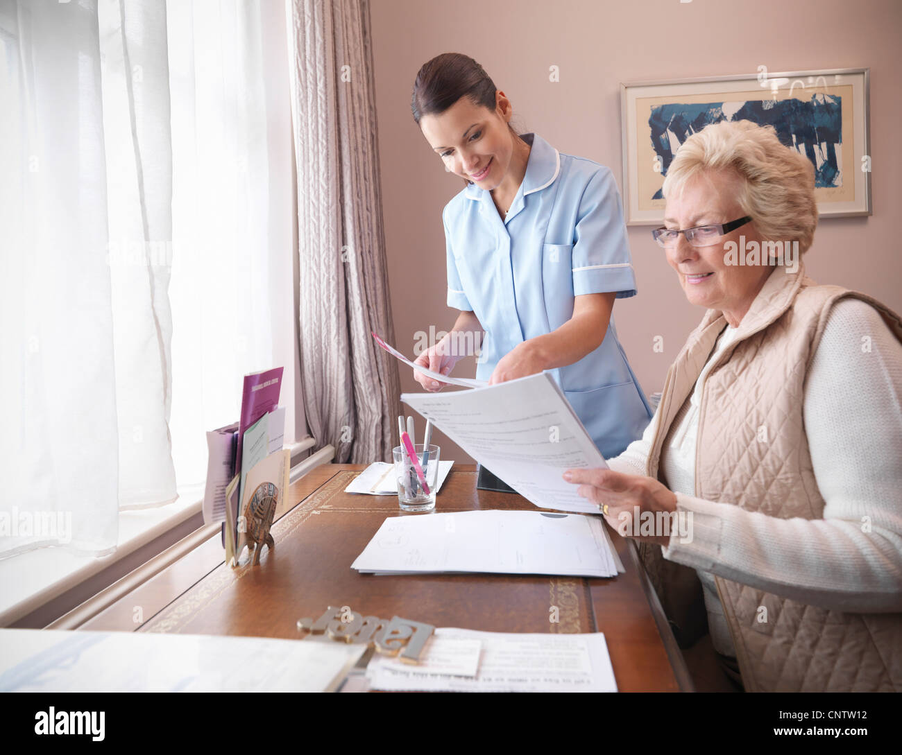 Older woman and nurse reading papers - Stock Image