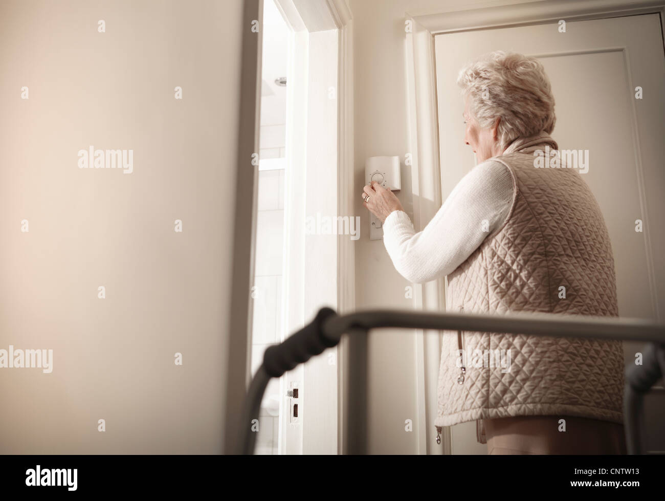 Older woman adjusting heating in house Stock Photo