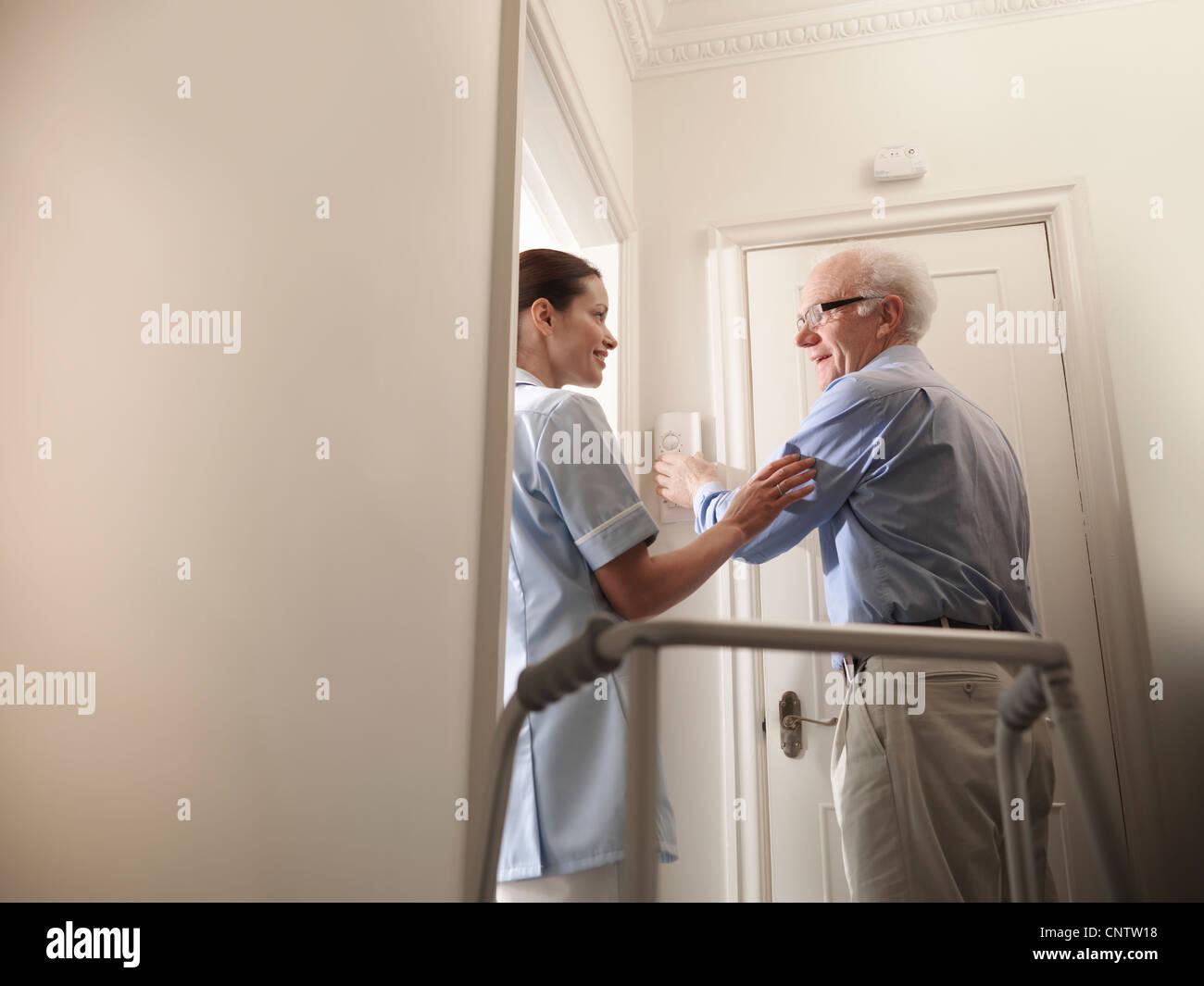 Nurse talking to older man in house - Stock Image