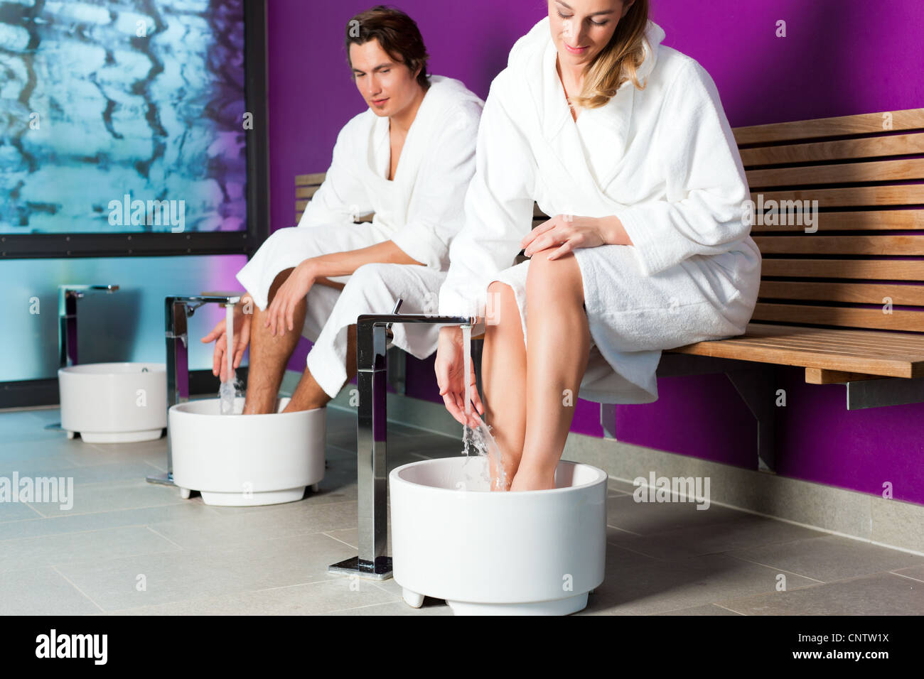 Couple - man and woman - having hydrotherapy water footbath in spa setting - Stock Image
