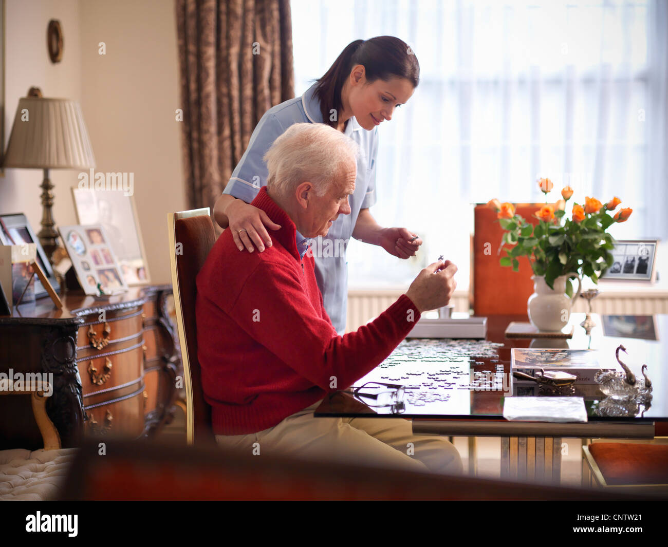 Nurse and older man doing jigsaw puzzle Stock Photo