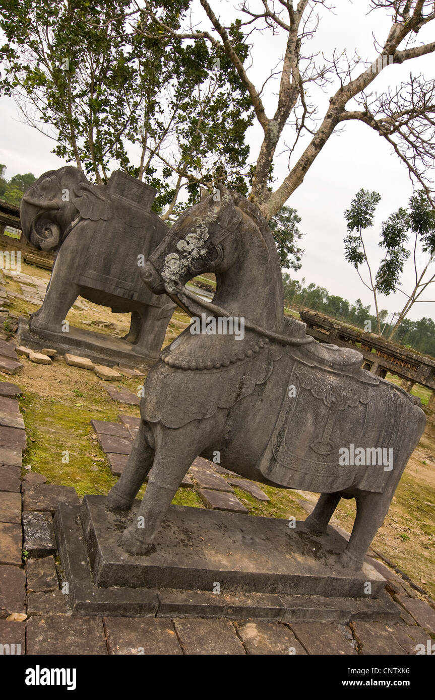 Vertical close up of large horse and elephant statues at the remains of the Tomb Of Emperor Tu Duc near Hue. - Stock Image