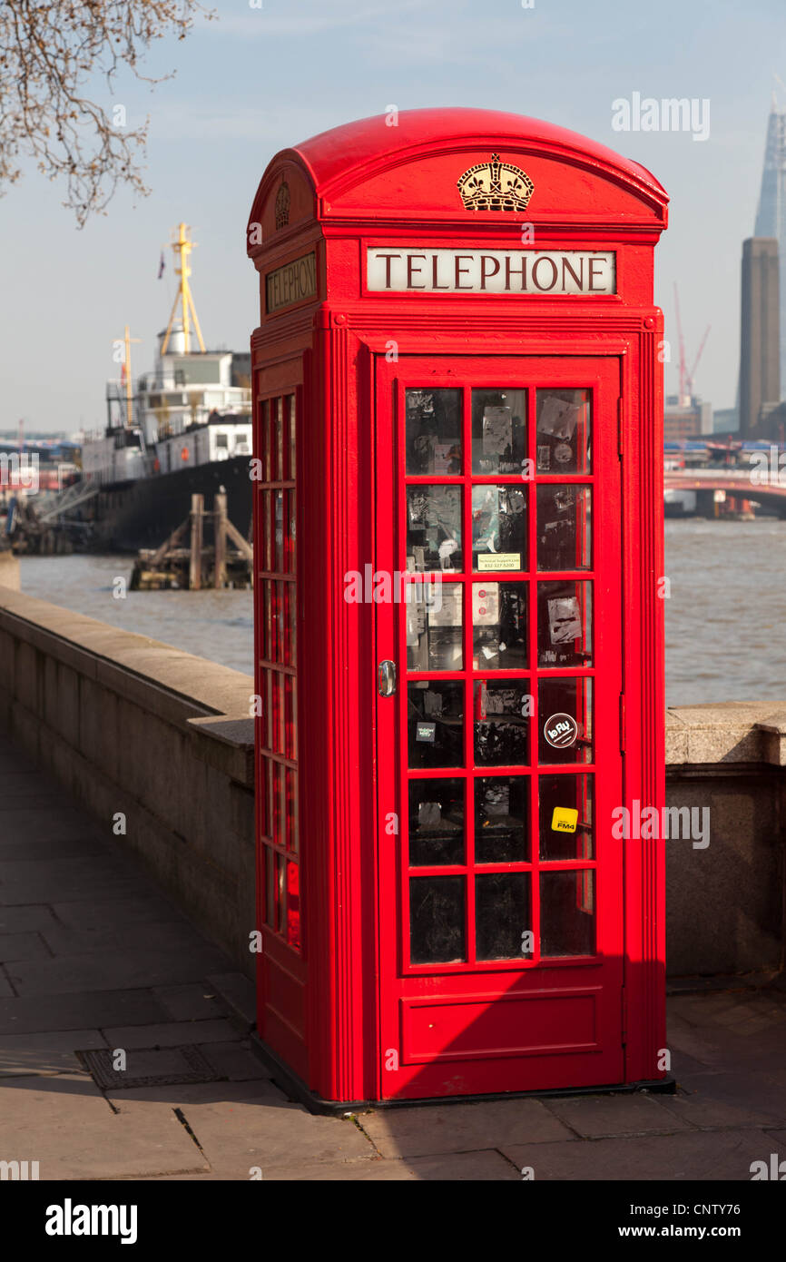 Red Telephone Box on banks of the River Thames London England - Stock Image