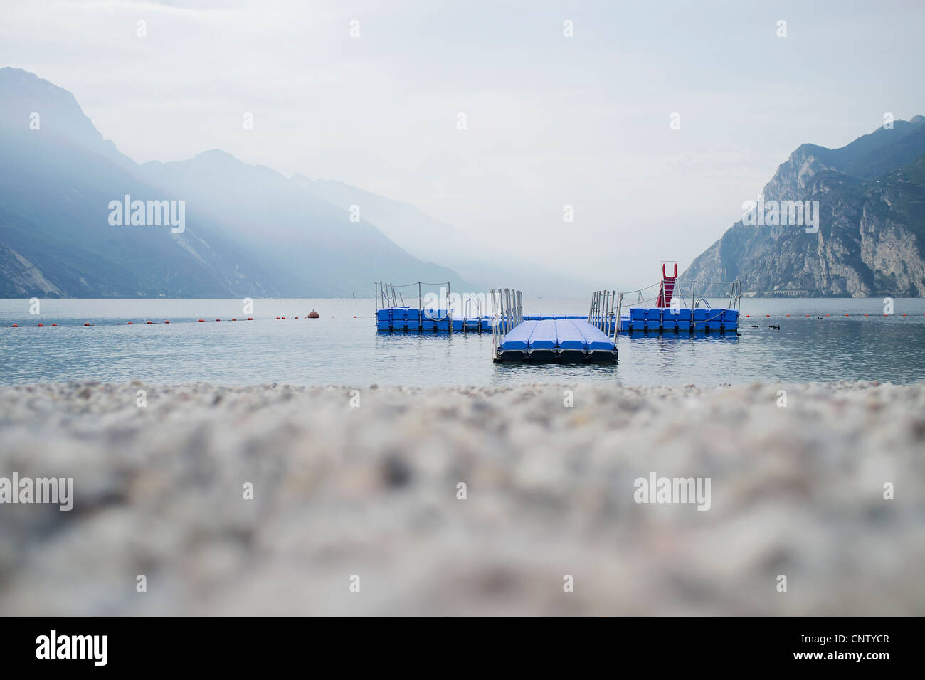 Floating pier off rocky beach - Stock Image