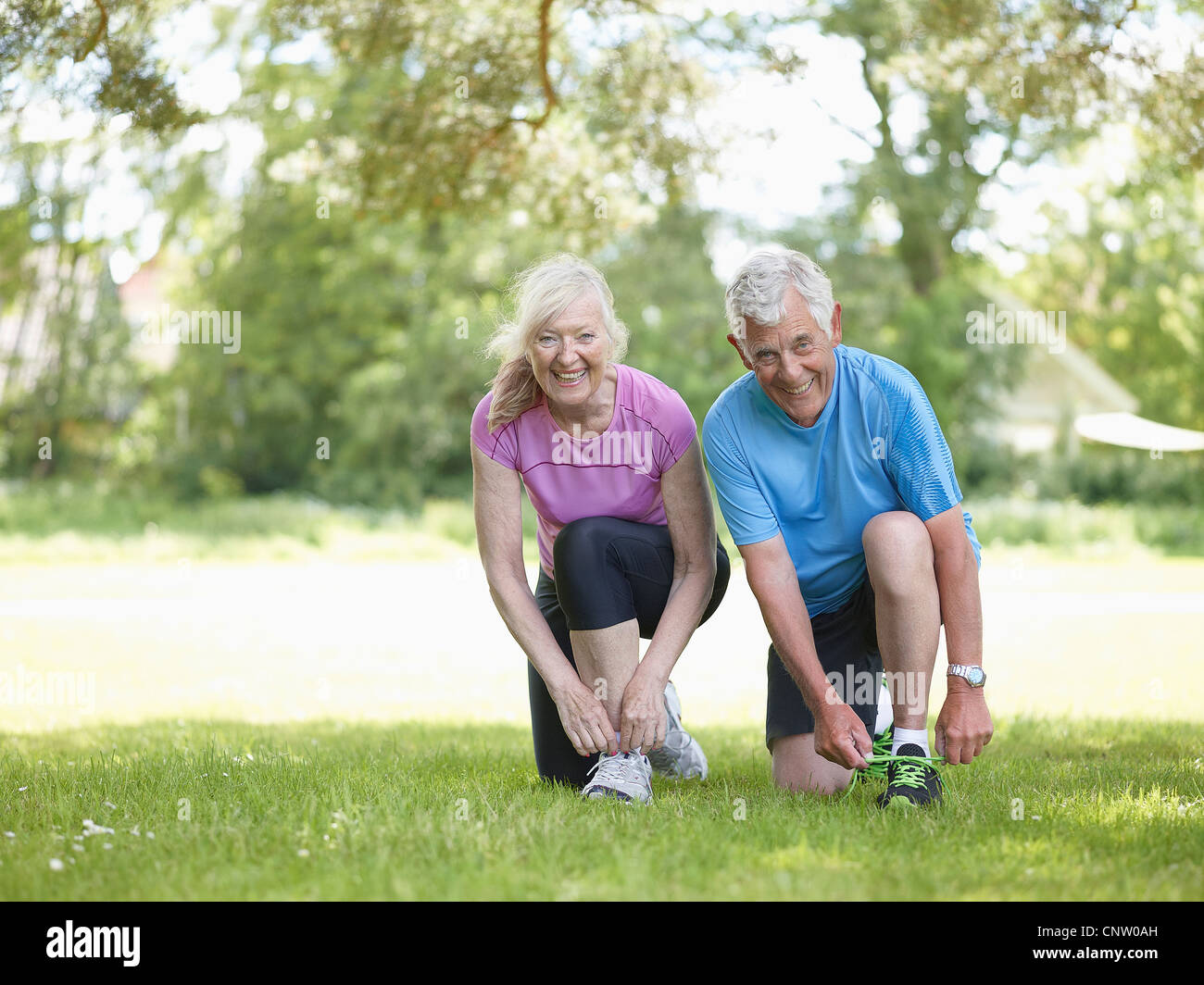 Older couple tying their shoelaces - Stock Image