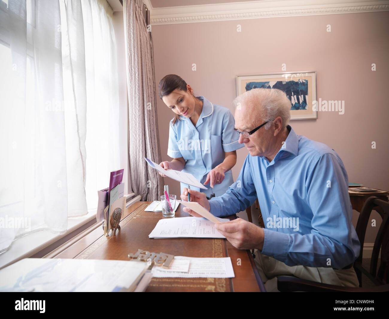 Older man and nurse reading papers - Stock Image