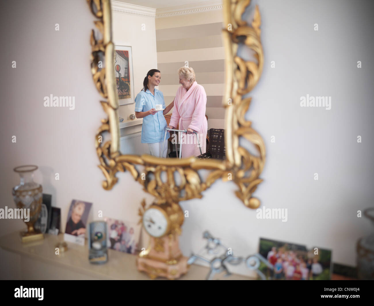 Nurse talking to older woman in house - Stock Image