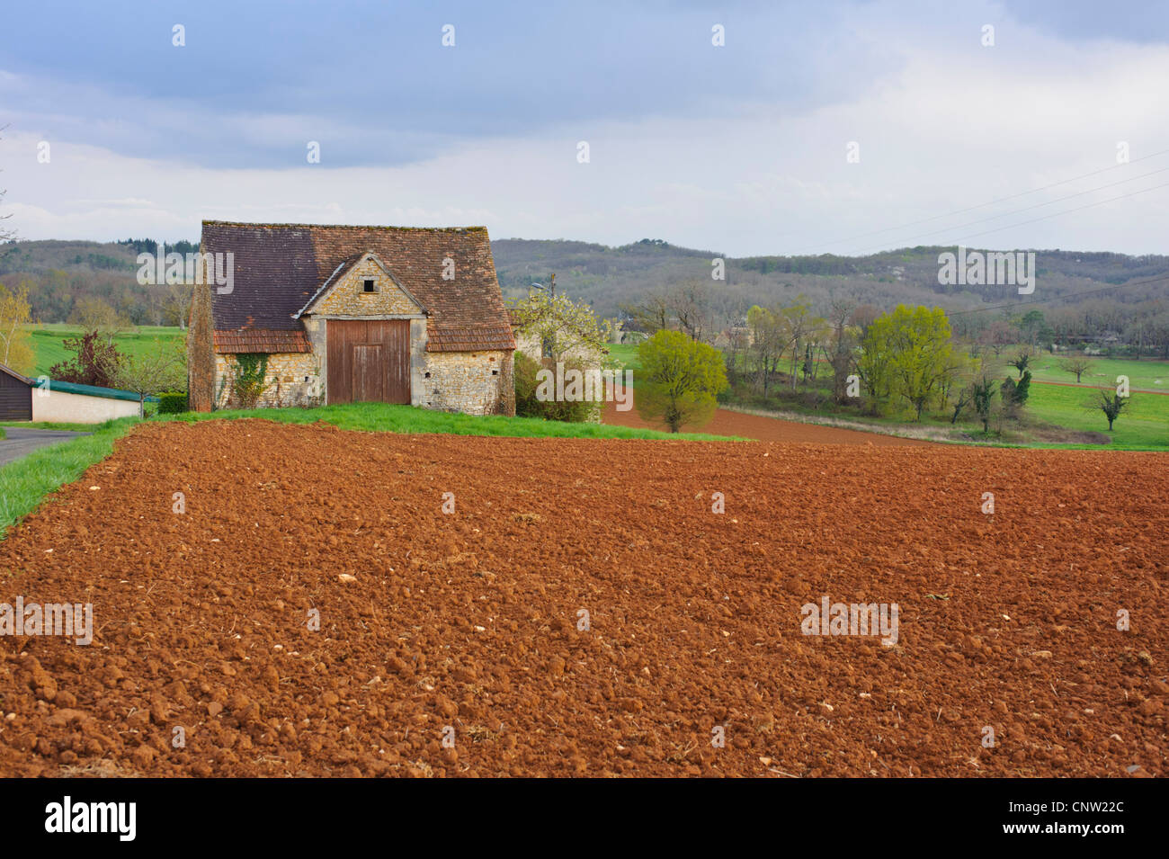 French farm barn and rich red soil in the department of Lot in southern France - Stock Image