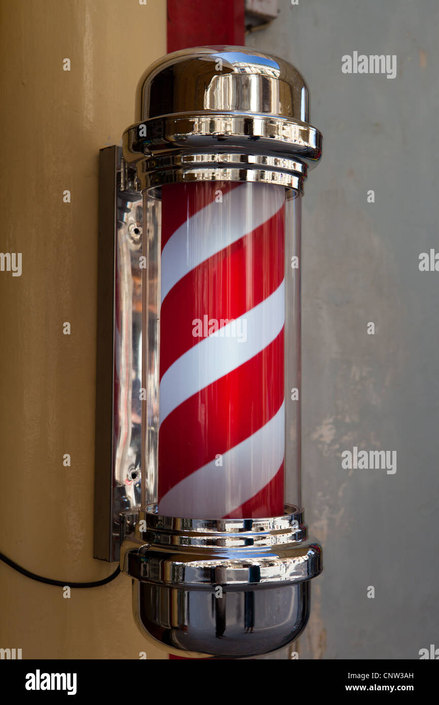 A traditional barber shop sign, illuminated and rotating - Stock Image