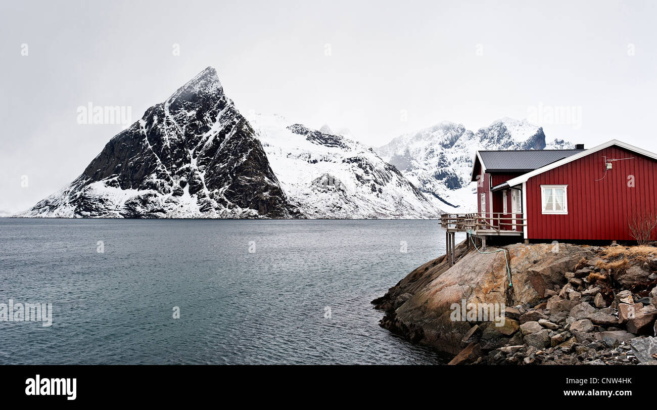A rorbu or fishermen's hut on the coast near Hamnoy, with Olstind mountain n the background - Stock Image