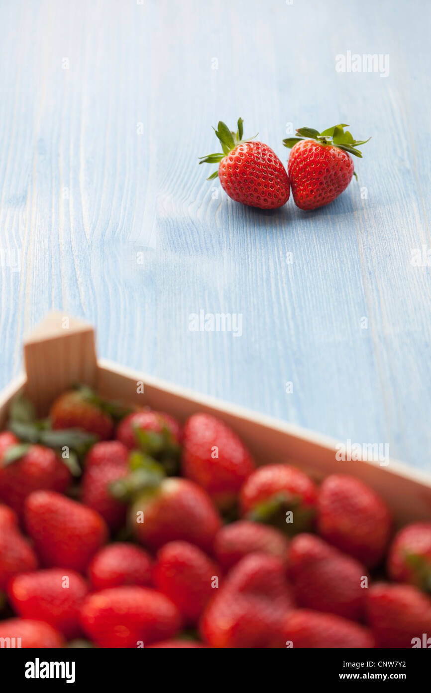 Pair of strawberries outside crate - Stock Image