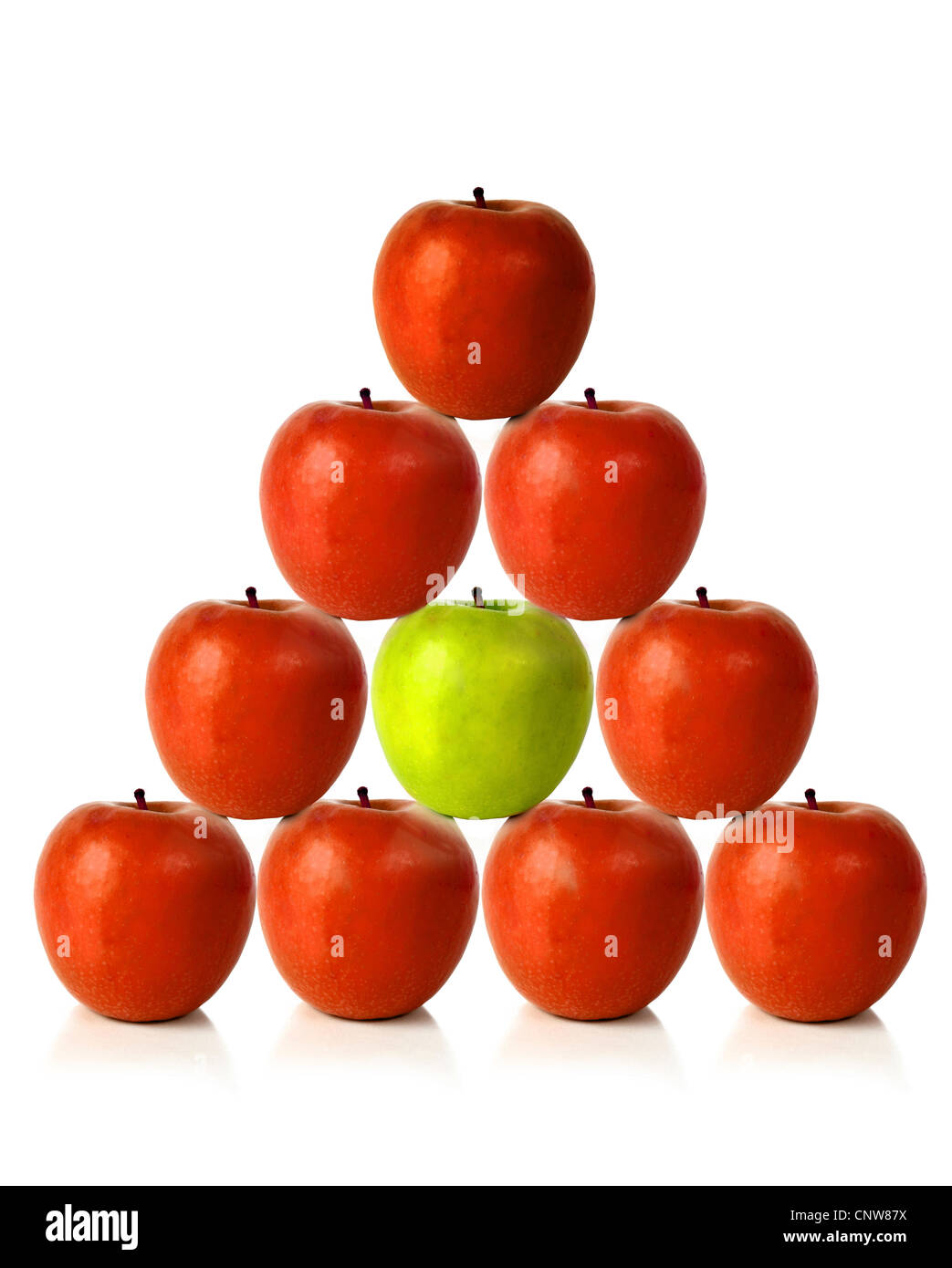 red apples on a pyramid shape with one green apple in the middle, be different Stock Photo