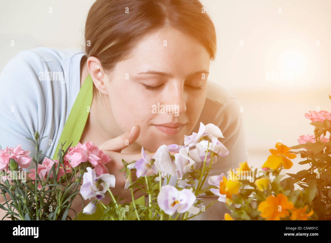 Woman smelling flowers plants indoors - Stock Image