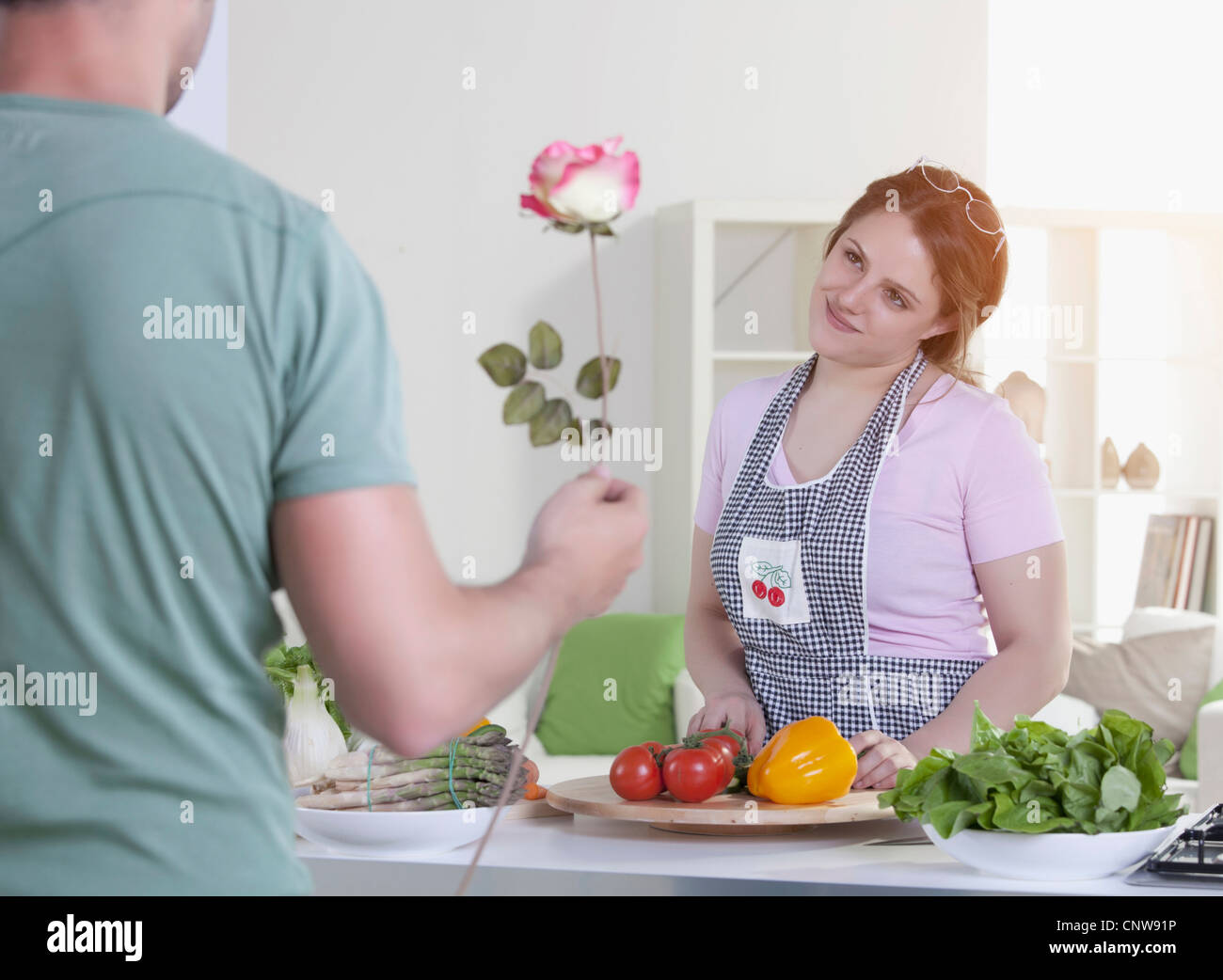 Man giving rose to cooking girlfriend - Stock Image
