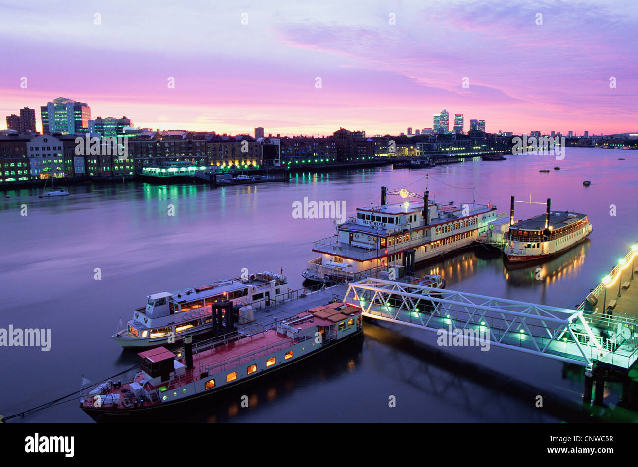 England, London, Night View of Boats on the Thames River with Docklands and Canary Wharf Skyline in Background Stock Photo