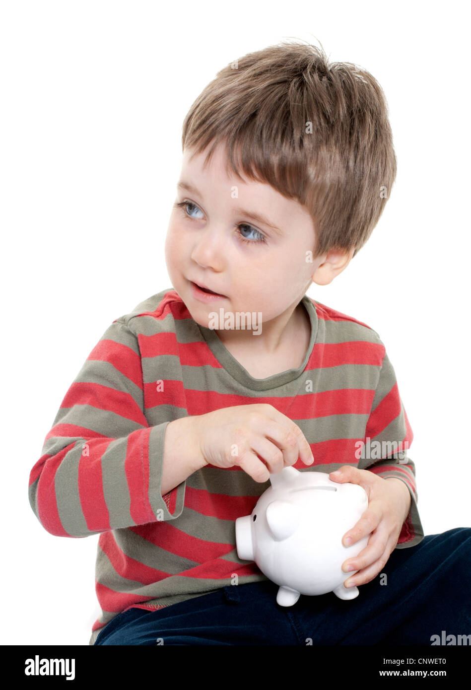 Young boy saving money in piggybank - Stock Image
