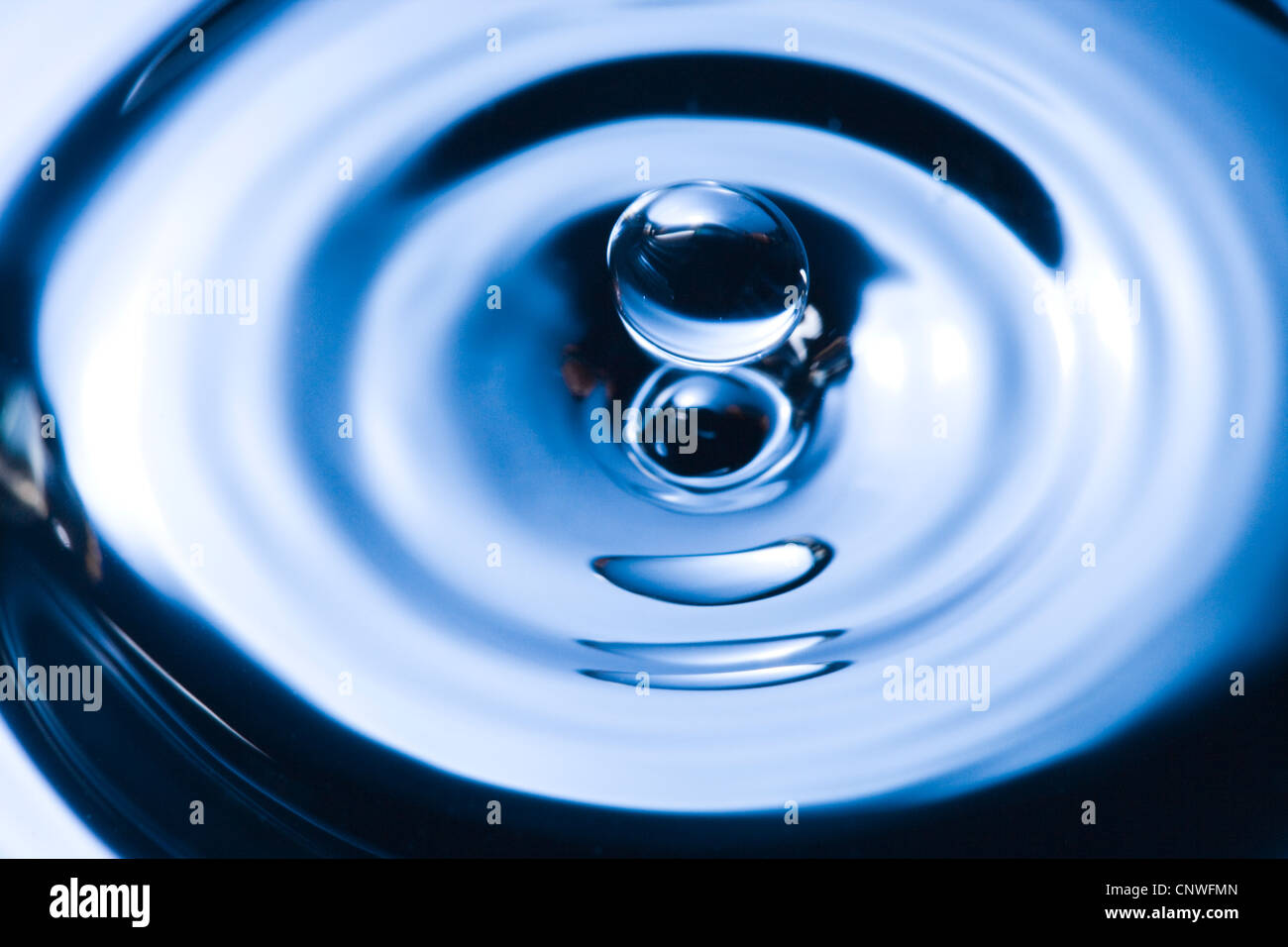 Water droplet causing ripples. Stock Photo