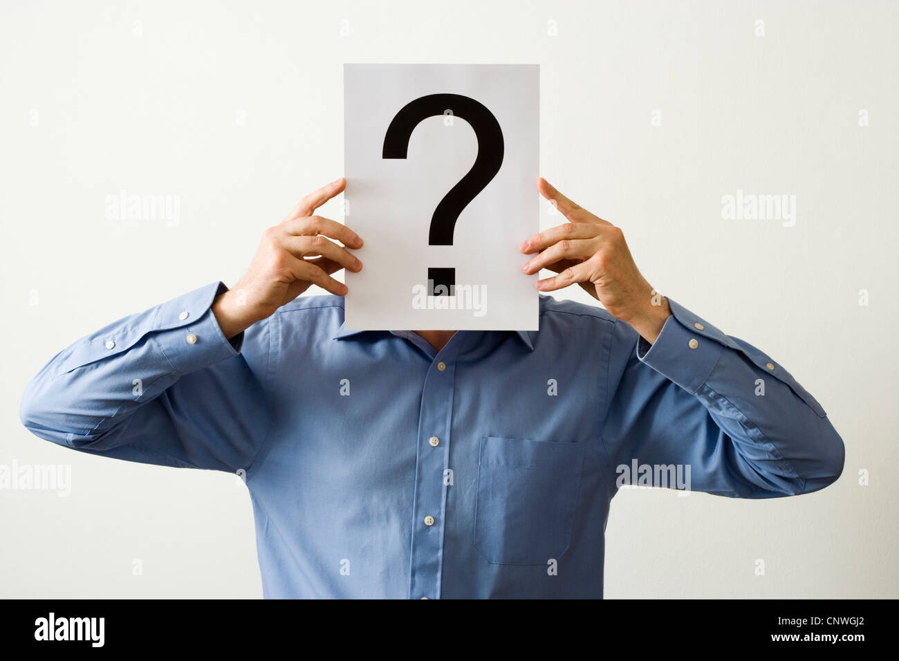 Man with question mark covering face. Stock Photo