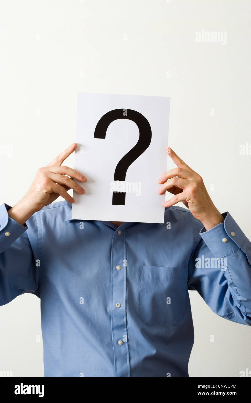 Man with question mark covering face. - Stock Image